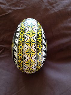 A traditional wheat and wave patterned pysanky with a