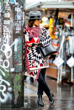 A print bold coat paired with a fedora and black ankle boots.