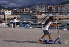 To each his own: A boy scoots past a girl more interested in the fishing boats in the harbor. Castro-Urdiales, Cantabria, Spain. Photo ©Mike Randolph