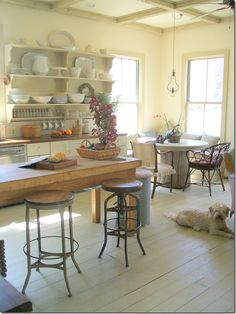 A wonderful arrangement of salvaged, vintage and antique. What I like most about this comforting space is the tree trunk table in the corner