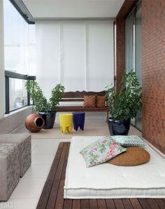 Relaxar e bater papo. Eis o que a moradora faz na porção da varanda reservada a um tablado de madeira com futon. Vasos esmaltados e banquinhos de polipropileno colorido atenuam a rusticidade. Projeto de Marcia Meccia.