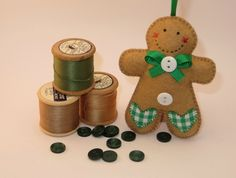 This gingerbread man is made of felt and handstitched using DMC cotton embroidery floss.  Decorated with green and white gingham fabric hearts,  green ribbon and white  buttons on the front, and a gingham heart and a metal 'Made with Love' charm on the back. This little Gingie is stuffed with new fi...