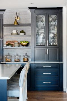 Chic contemporary kitchen features a glass front black china cabinet fixed above black cabinets donning long brushed brass pulls and beside black floating shelves stacked against gray grasscloth wallpaper lit by a Boston Functional Library Wall Light.