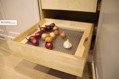 Specially designed onion and garlic drawer. The panel with perforated grid makes sure there is an air circulation around. The panel can be taken out of the drawer. Details like this show the true nature of a custom made kitchen. Eye for detail by the kitchen designer in Amsterdam.
