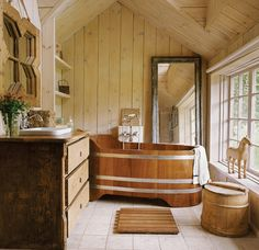 cozy cottage bathroom with wood tub and paneling