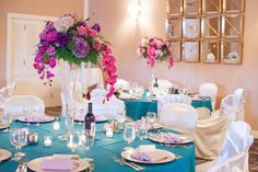 Tall centerpieces with orchids that cascaded down for a more dramatic look. Love the teal and purple colors