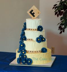 Round Wedding Cakes - Yellow ombre butter cream wedding cake with a Scrabble theme and blue gumpaste gerber daisies.
