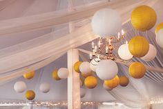 Paper lanterns in contrasting colors create a fun atmosphere for a tented reception.