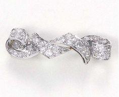 A DIAMOND BROOCH   Designed as a stylized circular-cut diamond ribbon