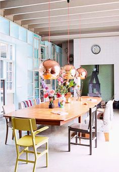 A fabulous home in a former garage. Tom Dixon copper light shades with neon pink cords.
