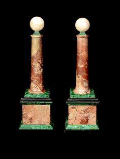 Two antique decorative columns/obelisks on shaped quadratic plints, red, pink and black marble, malachite, h. 28 cm.