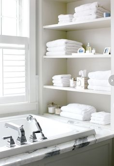 Open shelving  Open shelves at one end of the bathtub take advantage of an otherwise nonfunctional spot and offer storage ideas for bath towels and toiletries right where they're needed. Dramatically veined Calacatta marble on the tub deck provides a hit of pattern in the serene room.