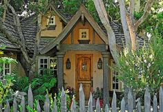 CUTE quaint storybook cottage home with weathered picked fence front yard