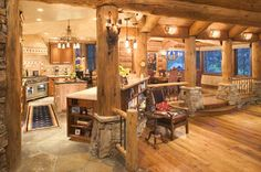 Warm log home kitchen with natural stone and large log posts