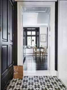 Mosaic tiles in the hallway of a Swedish home with dramatic black accents. Anders Bergstedt for Entrance.