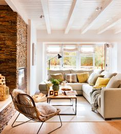 Salón con chimenea, sofá rinconero y detalle de pared de ladrillo