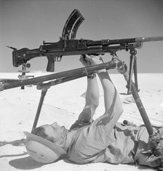 A British soldier works on a Bren gun at a field armory in the desert somewhere in Northern Africa.
