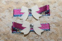 Little white bows with gem centers adorn a pair of ribbon lined alligator hair clip. The ribbon is pink satin with blue stitching. Great for Christmas! Clips are fully lined and come with non-slip gri