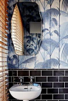 Dramatic powder room - black subway tile, blue and white print, white sink.