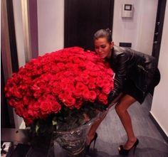 Büyük bir saksıdaki kırmızı güllerin içindeki tek taş yüzükle edilen evlilik teklifi.