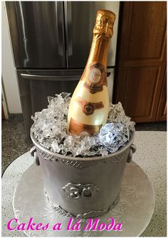 All edible champagne, ice bucket cake. Bottle made from chocolate with custom edible labels. Ice bucket all cake and fondant. Ice made from isomalt and underlit with LED lights.