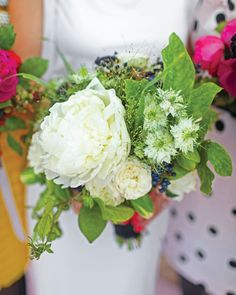 A variety of flowers such as peonies, roses, wild grasses, passionflower vine, viburnum berries, and nigella make up this interesting