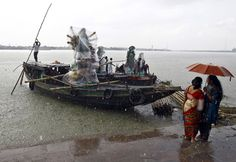 Devotees stand under an umbrella as the idols of Durga are being transported on boats through the waters of river Ganga during a rain shower in Kolkata.