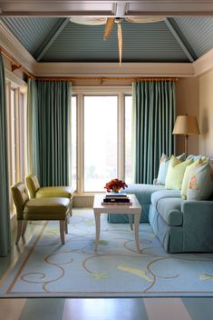 eclectic sun room with white blue stripes floors blue rug with simple motifs blue sofas with pillows green chairs white center table blue half way curtains of Ultimate Choices of Half Curtain Design for Home