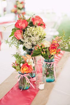 Reception/ Decorations : Pretty blue mason jars with flowers saturated in color!