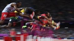 Aries Merritt of the United States leads Jason Richardson of the United States and Hansle Parchment of Jamaica in the Men's 110m Hurdles Final on Day 12.