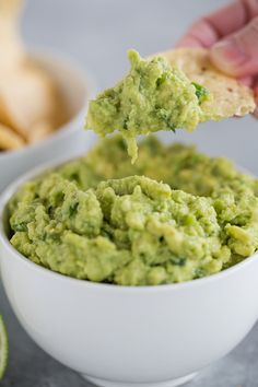 Someone holding a tortilla chip with a scoop of guacamole on it.