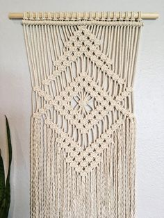 This macrame wall hanging is handmade with 1/8 organic cotton rope and a wooden dowel. It measures 18 across and about 40 down. This small macrame wall hanging is the perfect way to add texture to your home. Use as part of an art collection or as a statement piece. Buy it for yourself