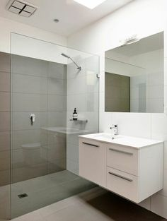"""A Breezy Modern Beach House Sits Among the Trees in Australia - Photo 5 of 8 - """"Keeping the kitchen and bathrooms simple saved money for the important things,"""" Harkness explains. They went with a soothing color palette and hardware from Reece."""