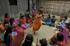 A girl dances to a folk song in the centre of group of adolescents, all of whom are girls, in the municipality of Driver Para, in Gaibandha District of Bangladesh. The adolescents are part of a community group that is discussing plans to speak to local residents about hygiene practices. Adolescent community groups are organized by UNICEF, the international NGO CARE and the Government to raise awareness about community and environmental sanitation. © UNICEF/Shehzad Noorani…