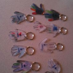 Key chains the daycare kids can make. Made from shrinky dink paper/plastic found in any craft store. Put a hand print on the paper and write a message in the hand. Pop it in the oven and you have miniature hand keychains. Great Mother's/Father's Day present :)