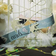 A paper streamer to dress up our modern or classic birdcage. Meant to weave through the bars of the birdcage, comes in a variety of colors for the love birds. Available for purchase online http://madelinesweddings.weddingstar.com/product/personalized-streamer-for-cards