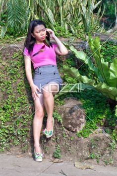 beautiful female talking on the phone. - Front view shot of a attractive young lady talking on her cell phone. Model: Claire Raterta