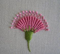This flower's spokes are not just made from straight stitches, but long chain stitches. Once the whipping is done, the sides of each chain are pulled together to form the diamonds at the top. This is from Jane Nicholas' book Stumpwork Embroidery.