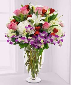 Abundance of Love: Make her heartbeat with this luxurious gathering of pink roses, white hydrangea, white lilies, purple dendrobium orchids and accents of red hearts elegantly designed in a clear glass pedestal vase by Central Square Florist
