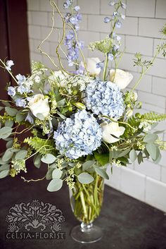 Classic look-hydrangeas, white flowers, and tall curvey sticks. I see some fern in there too.