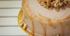 Caramel cake sitting on a gold platter on a white table while decorated with tan frosting, caramel corn, and caramel drizzles.