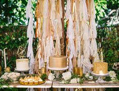 gold and white dessert table with gold cakes + tassels + cake toppers