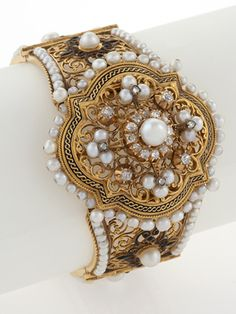A French Napoleon III 18 karat gold bracelet with diamonds and pearls. The bracelet features 20 old mine-cut diamonds with an approximate total weight of 1.20 carats, and 168 natural freshwater pearls. The bracelet is composed of 6 pierced gold plaques with enamel detailing and a central pearl, diamond and enamel oval plaque. In the original fitted box. Circa: 1860's