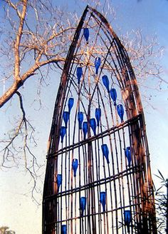"A ""stained glass"" window made from branches and glass bottles.  How fun would this be in the garden."