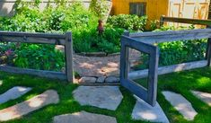 short wire gate around herbs in backyard-- boarder beds with stones--- stepping stone path to herb garden