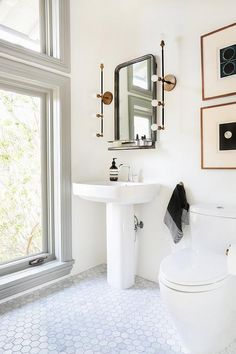 Modern bathroom features a Restoration Hardware Astoria Mirror with Shelf illuminated by brass linear sconces, Apparatus Studio Vanity Sconces, over a pedestal sink atop a marble hex tiled floor placed in front of large, stacked windows framed in grey moldings.