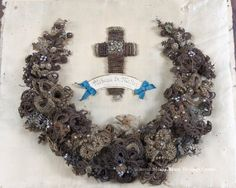 A wreath, constructed of human hair. The name on the hair woven cross says Rebecca Miller. Hair wreaths were common in the victorian period.