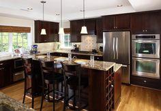 Eine Kücheninsel steht nur über den arbeitsreichen Dreieck von dieser u-förmige zeitgenössische Küche groß. Foto von AHMANN LLC