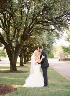 A kiss under the beautiful oak trees: http://www.stylemepretty.com/oklahoma-weddings/2016/09/09/classic-country-club-summer-wedding/ Photography: Magnolia Adams - http://magnoliaadamsweddings.com/