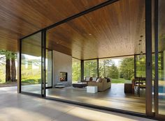 Living/dining room/wraparound patio of a glass house in Sonoma County by architects Leslie and Julie Dowling